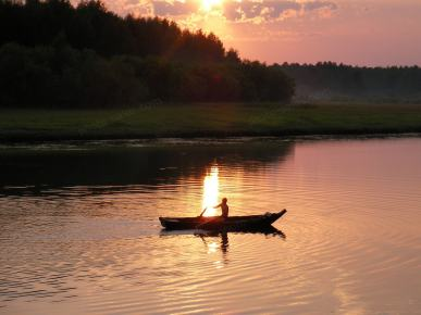 A man in a boat at sunset