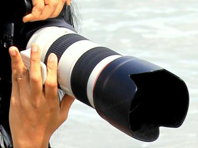 Photo camera with large lens in hands