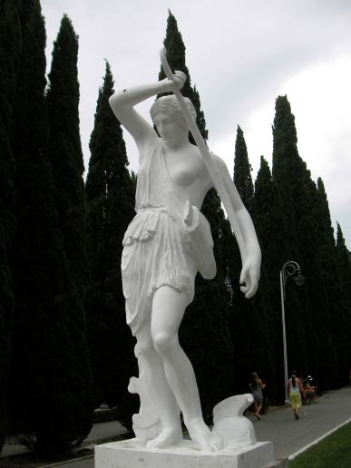 Statue of a woman with bare breast and bow