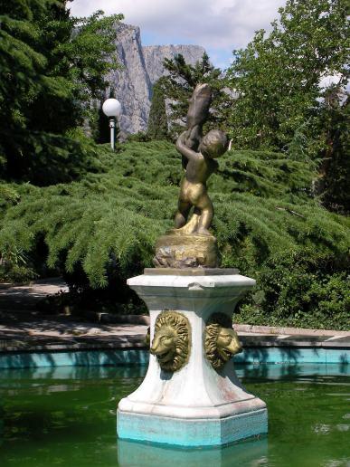 Statuja e djalit të artë me një peshk