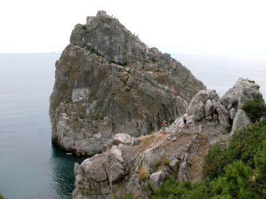Tourists climb on the rock Diva in Simeiz in Crimea